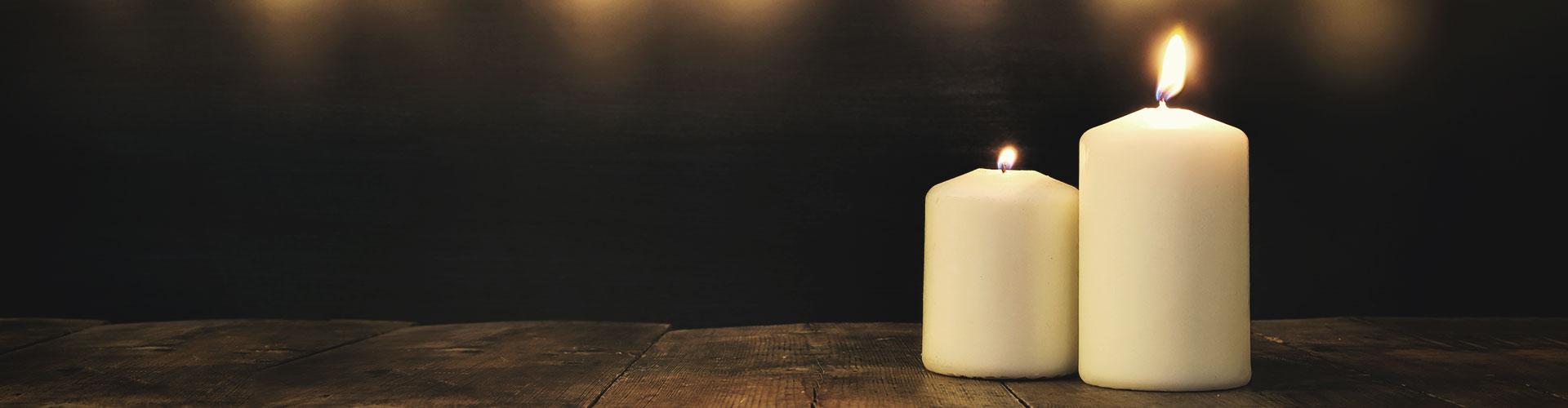 Zwei brennende Kerzen stehen vor einem dunklen Hintergrund