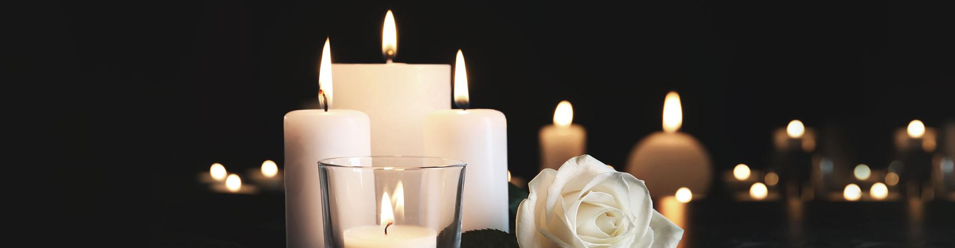 Viele weiße Kerzen vor schwarzem Hintergrund