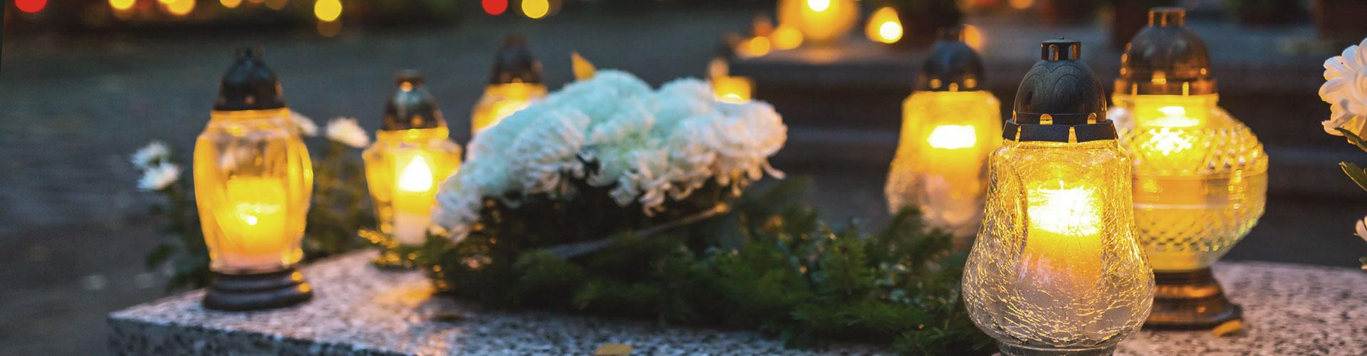 Brennende Kerzen und weiße Blumen auf einem Grabstein