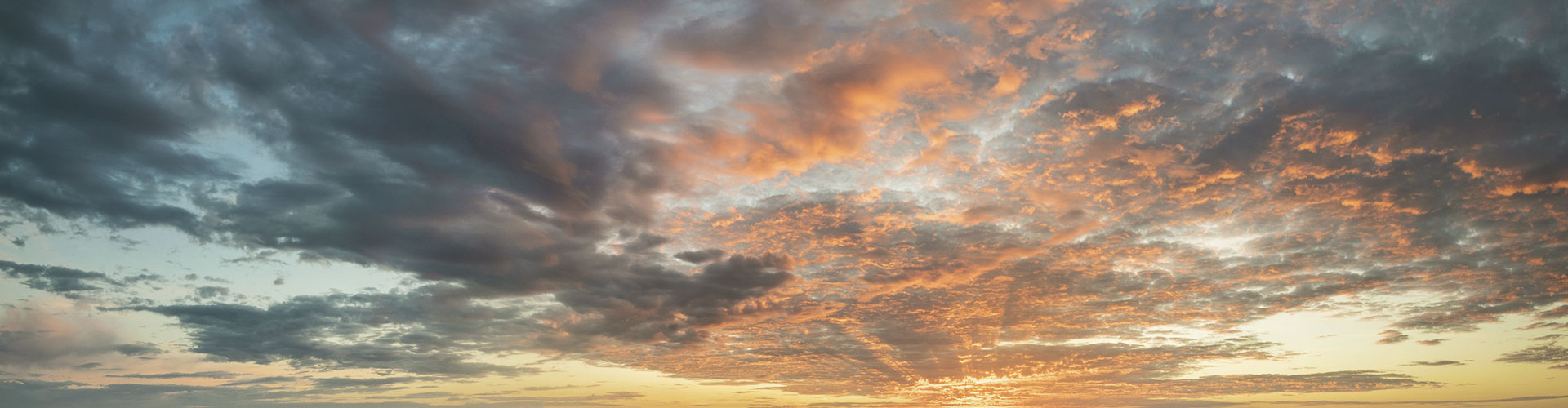 An einem bewölkten Himmel geht die Sonne langsam unter