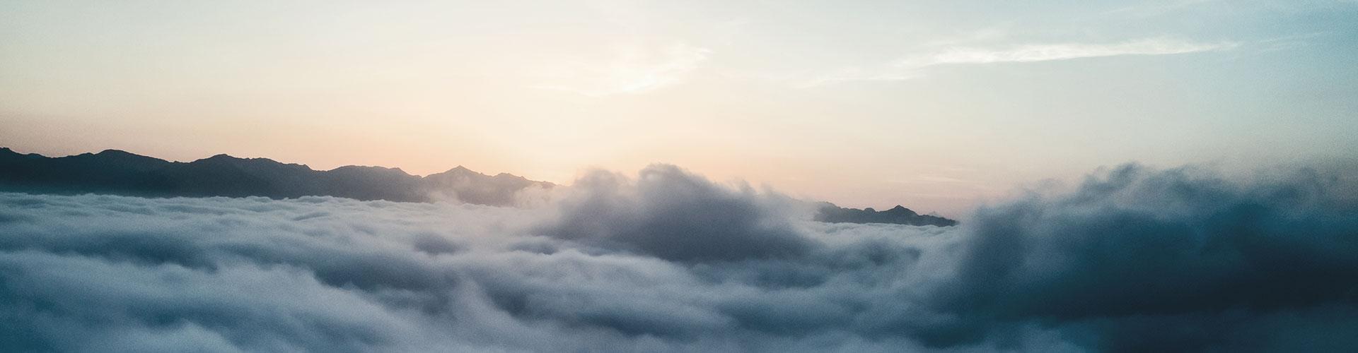 Nebel liegt über einem Tal, der Himmel ist pastellfarben