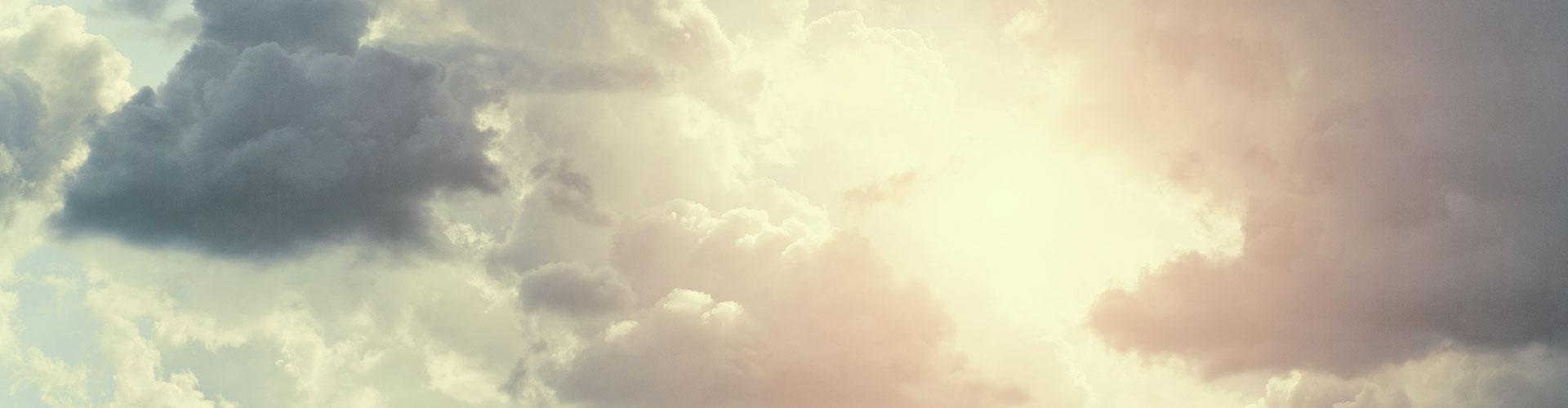 Helles, warmes Licht bricht durch eine dunkle Wolke