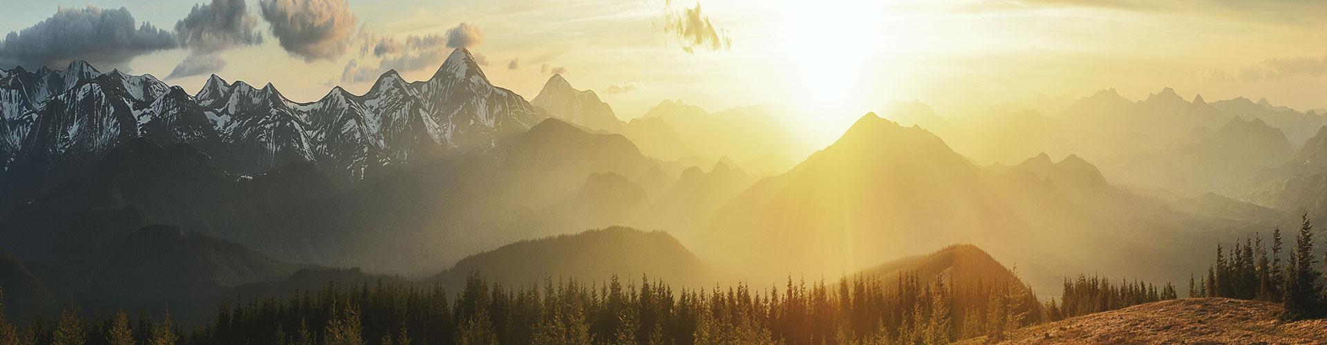Die Sonne taucht eine bergige Landschaft in goldenes Licht