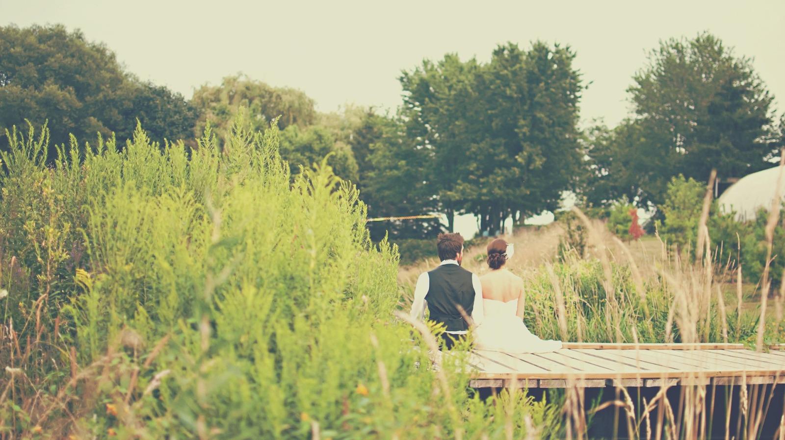 Ein Hochzeitzpaar sitzt auf einem Steeg in freier Natur