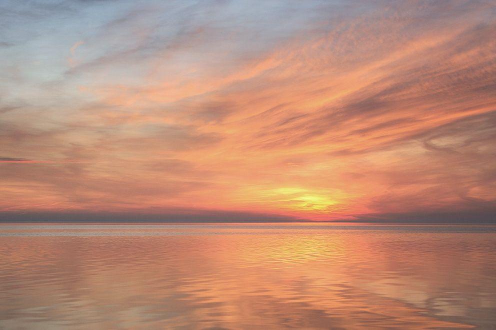 Über einem See geht die Sonne unter