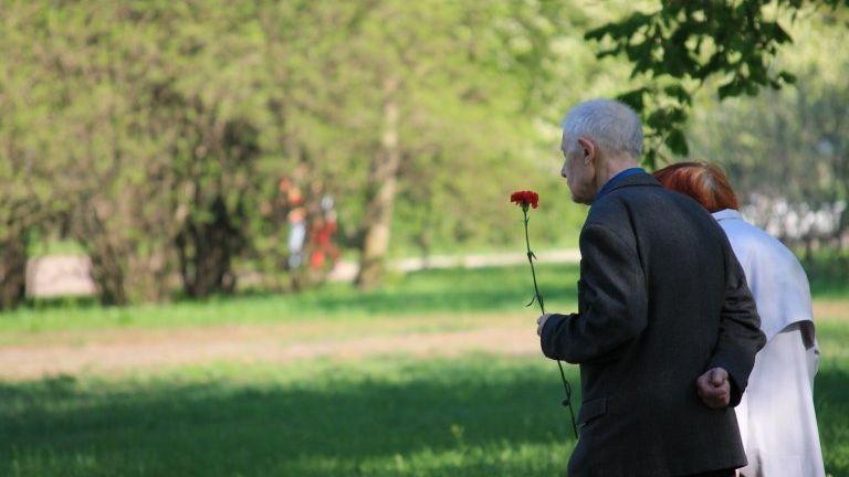 Ein älteres Paar geht auf einem Rasenfriedhof