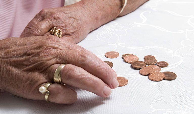 Eine ältere Dame zählt Kleingeld auf einem Esszimmertisch.