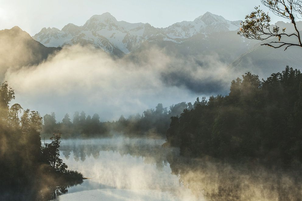 Ansicht eines Sees bei Nebel, im Hintergrund Berge