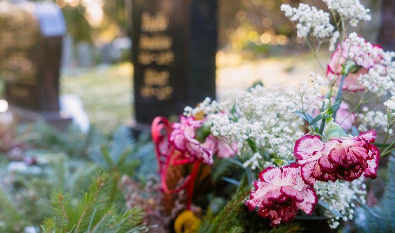 Blumen und Grabsteine auf einem Friedhof.