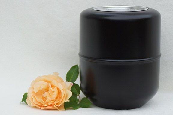 Foto einer schwarzen Aschekapsel und einer Rose