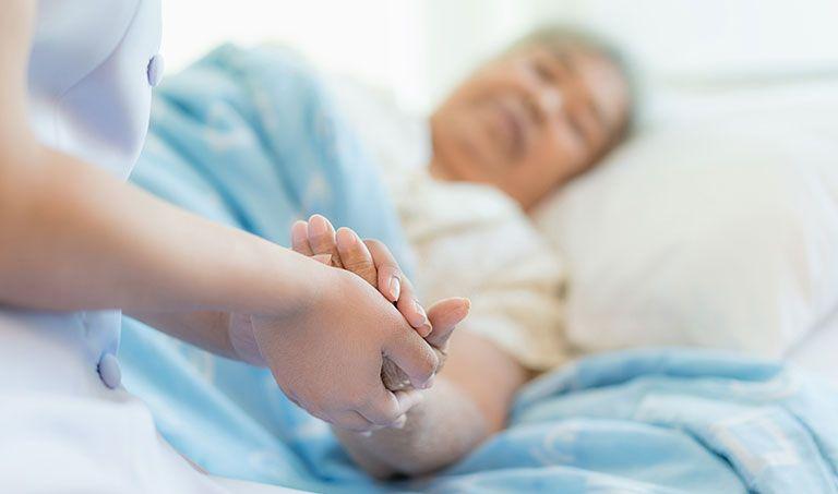 Eine Pflegerin hält im Krankenhaus die Hand einer Frau.