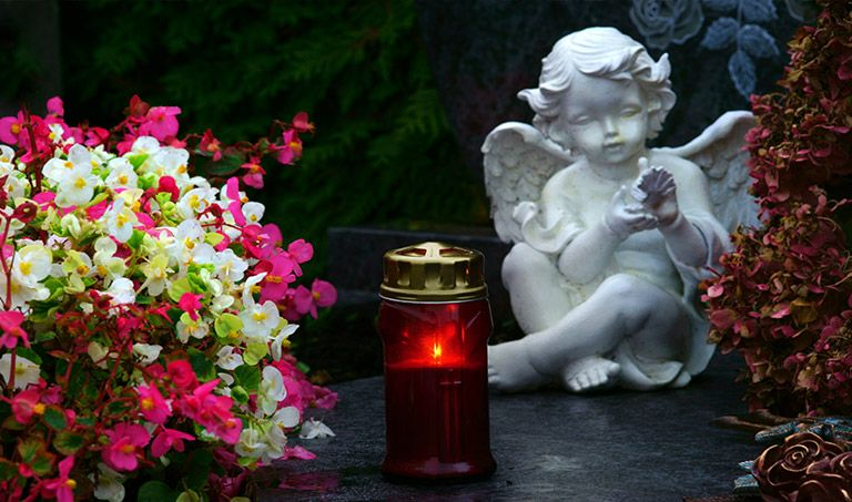 Grabschmuck, Blumen und eine Grabkerze auf einem Grab.