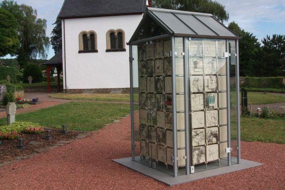 Außen stehendes Kolumbarium mit einer Kapelle im Hintergrund