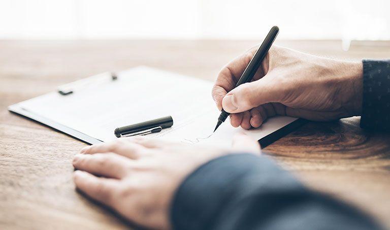 Ein Mann unterschreibt ein Testament, um seinen Nachlass zu regeln.
