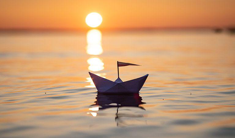 Ein Papierschiff schwimmt auf einem See. Im Hintergrund geht die Sonne unter.