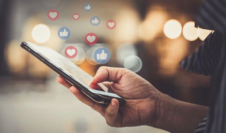 Ein junger Mensch hält ein Smartphone in der Hand, über dem Likes aus sozialen Netzwerken schweben.