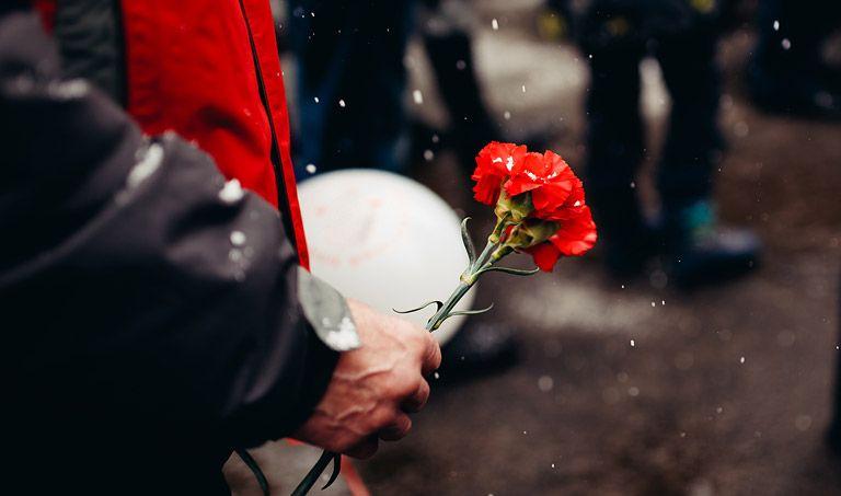 Eine Frau steht mit einer roten Blume auf einer Trauerfeier.