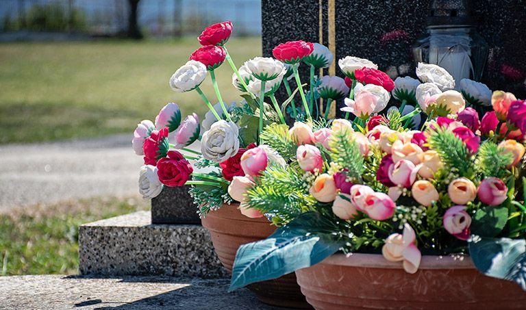 Blumentöpfe mit bunten Blumen auf einem Grab