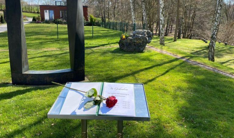 Ein Buch mit einer Rose steht auf einem Pult auf einem Friedhof