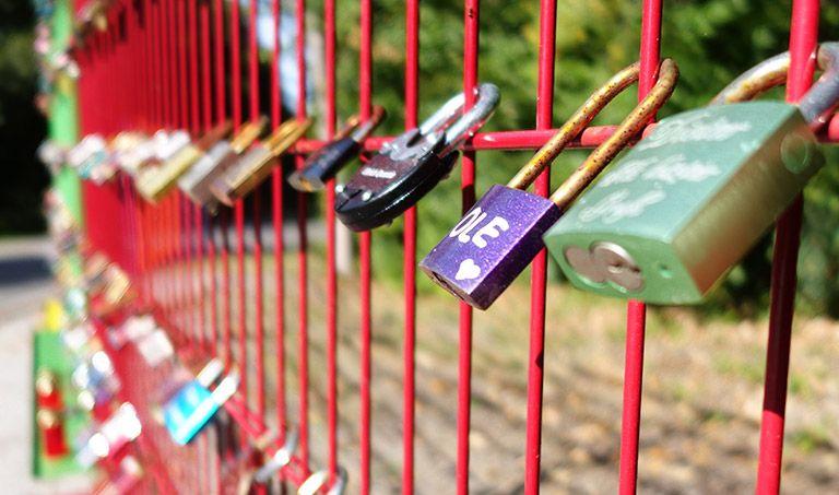 Bunte Metallschlösser mit Namen sowie Geburtsdaten und Sterbedaten sind an einem roten Zaun befestigt.