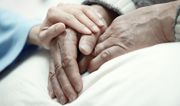 Eine junge Hand liegt auf alten Händen.
