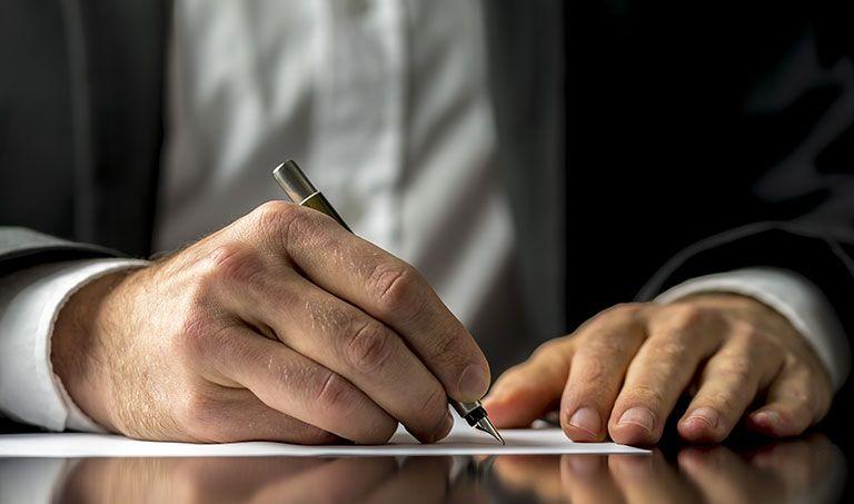 Ein Mann im Anzug verfasst handschriftlich sein Testament.