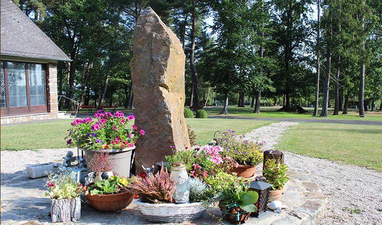 Blumen und Andenken stehen an einem Gedenkrondell