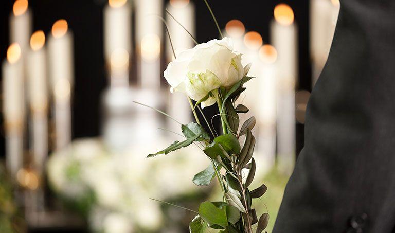 Weiße Rosen und Kerzen bei einer Trauerfeier