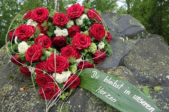 Ein Herz aus roten und weißen Rosen als Grabdekoration
