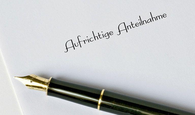 """Auf einem Kondolenzschreiben mit der Aufschrift """"Aufrichtige Anteilnahme"""" liegt ein Füller."""
