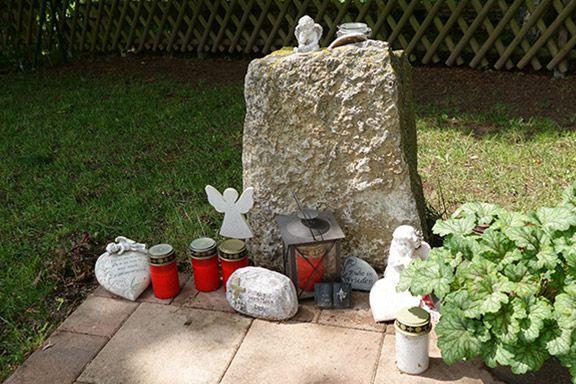 Dekorative Steine mit Engelsfiguren und Grabkerzen Friedhof Horrweiler