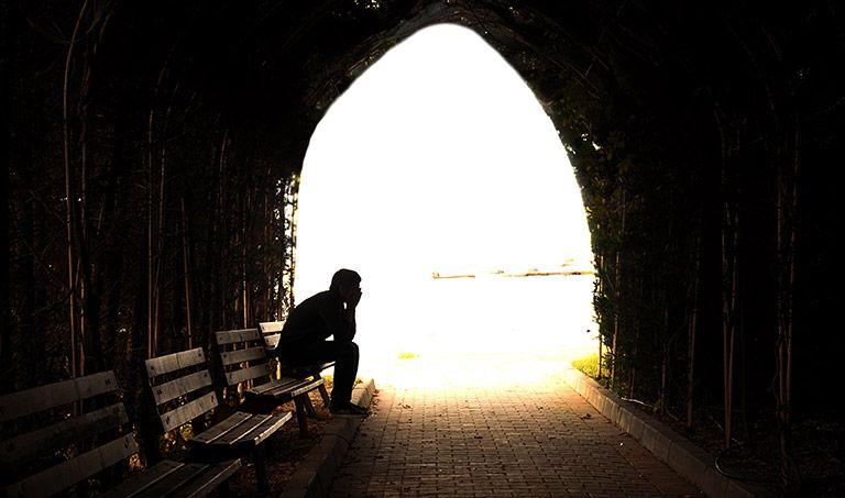 Ein Mann sitzt im Gegenlicht in einem dunklen Tunnel.