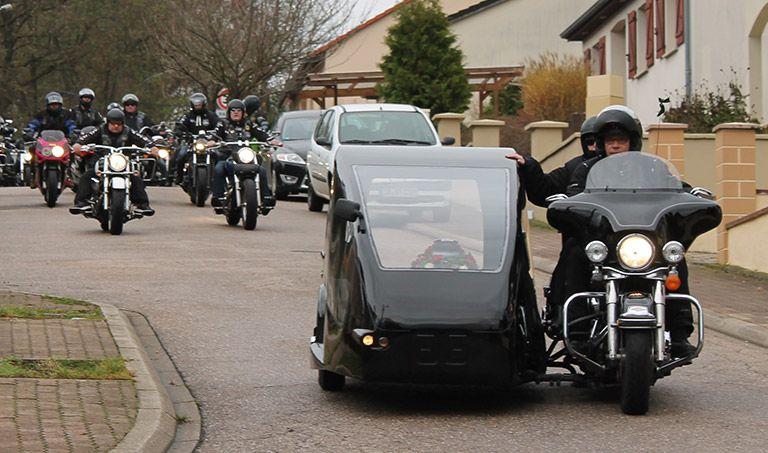 Eine Urne wird in einem Motorrad mit Beiwagen transportiert. Im Hintergrund folgen weitere Motorräder als Konvoi.
