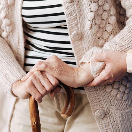 Eine Pflegerin hilft einer alten Dame mit einem Stock beim Laufen.
