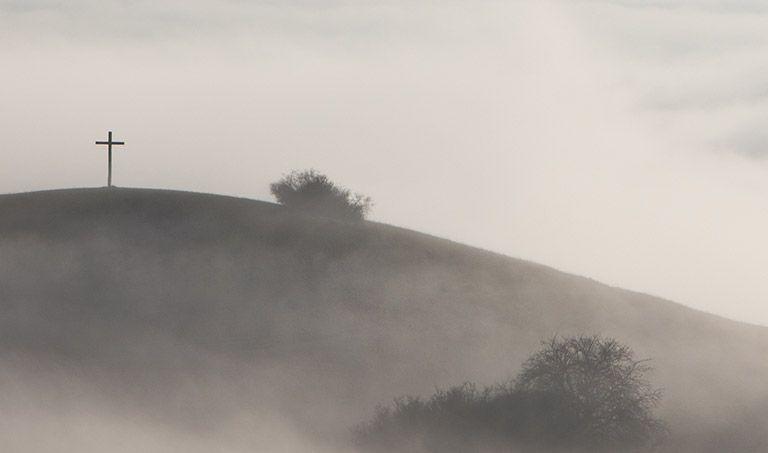 Ein schmales Kreuz steht im dichten Nebel auf einem Gipfel.